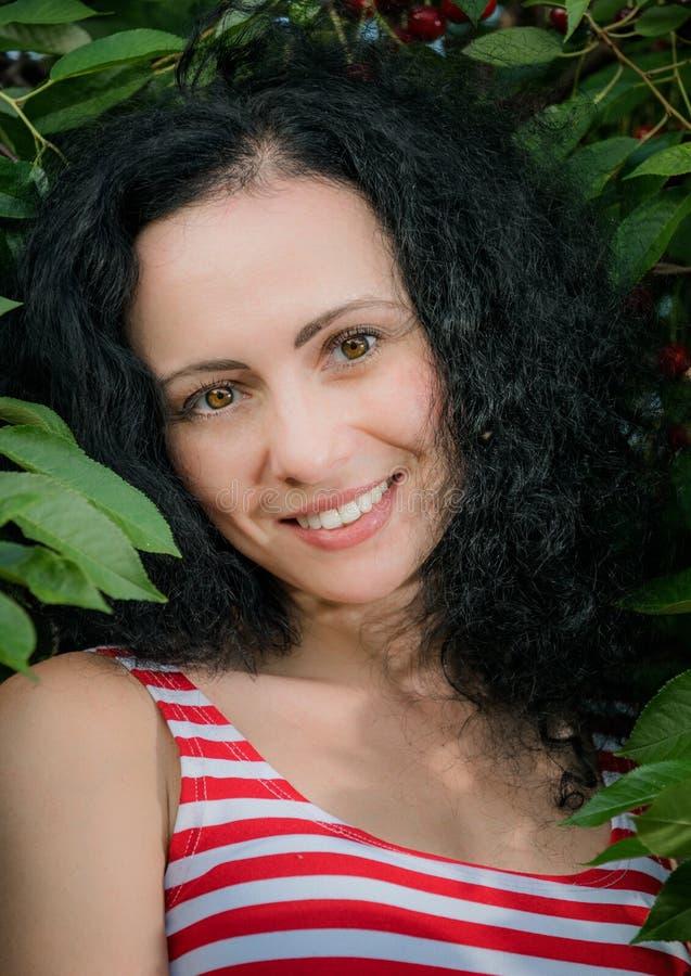 Красивая молодая женщина в саде вишни лета стоковое изображение rf