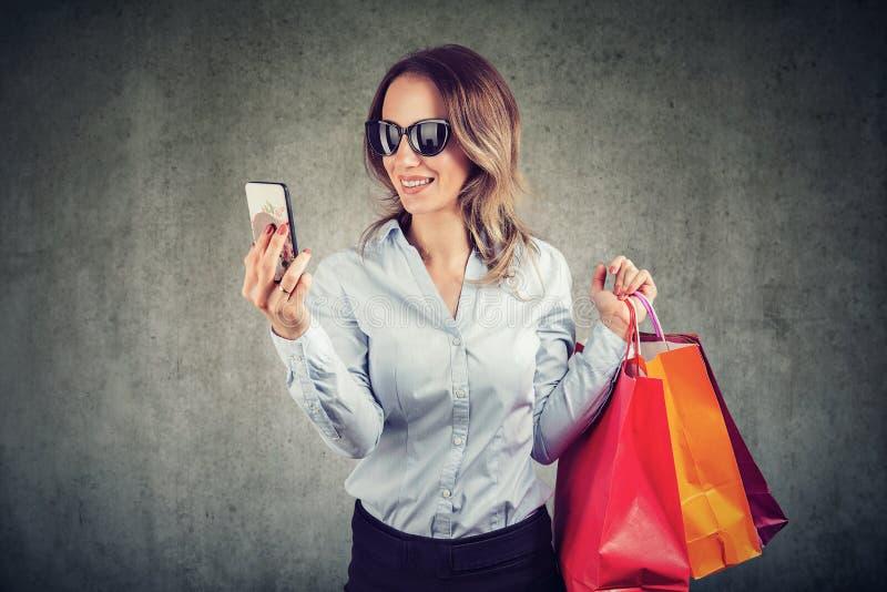 Красивая молодая женщина в солнечных очках идет ходить по магазинам стоковое изображение rf
