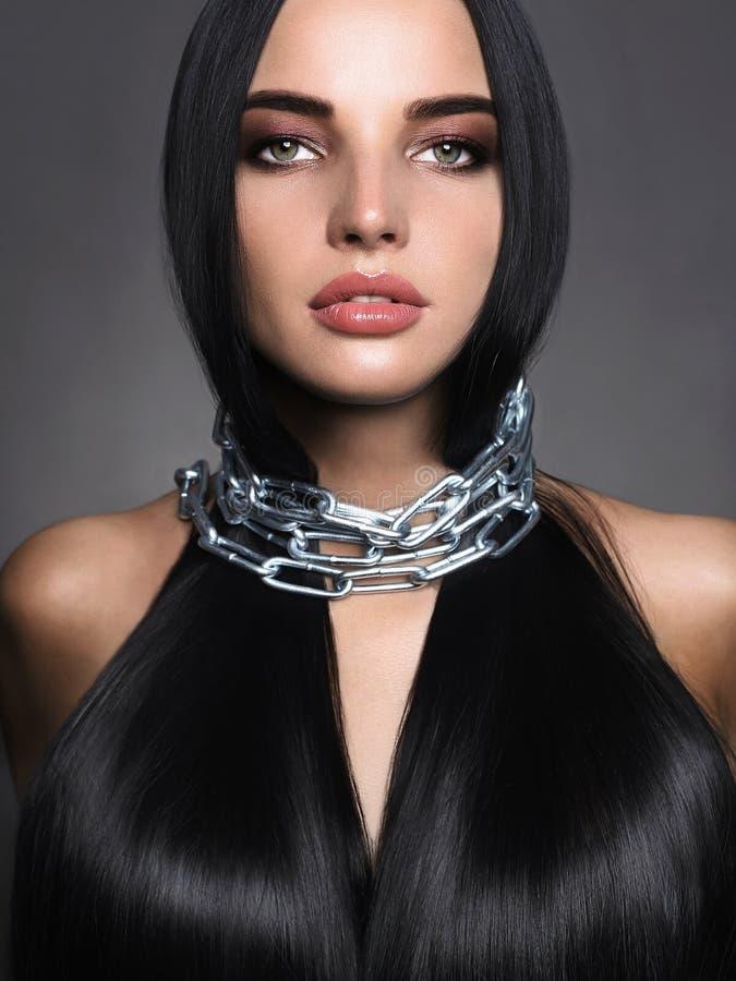 Красивая молодая женщина в стальной цепи стоковое фото rf
