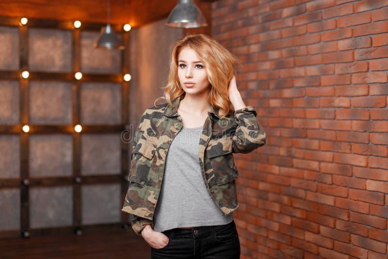 Красивая молодая женщина в стильной куртке около кирпичной стены стоковое фото