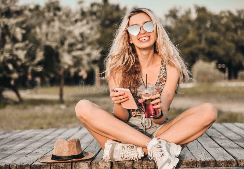 Красивая молодая женщина в стильной шляпе с холодным коктейлем имеет outdoors потехи стоковое фото
