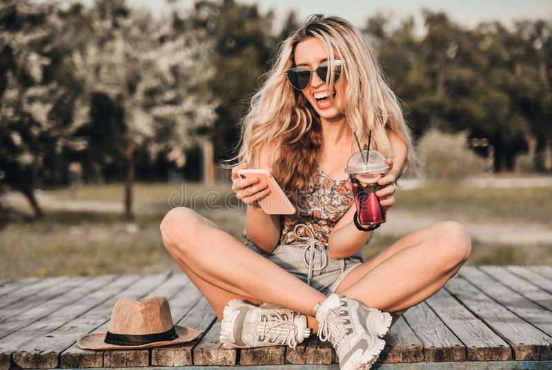 Красивая молодая женщина в стильной шляпе с холодным коктейлем имеет outdoors потехи стоковая фотография rf