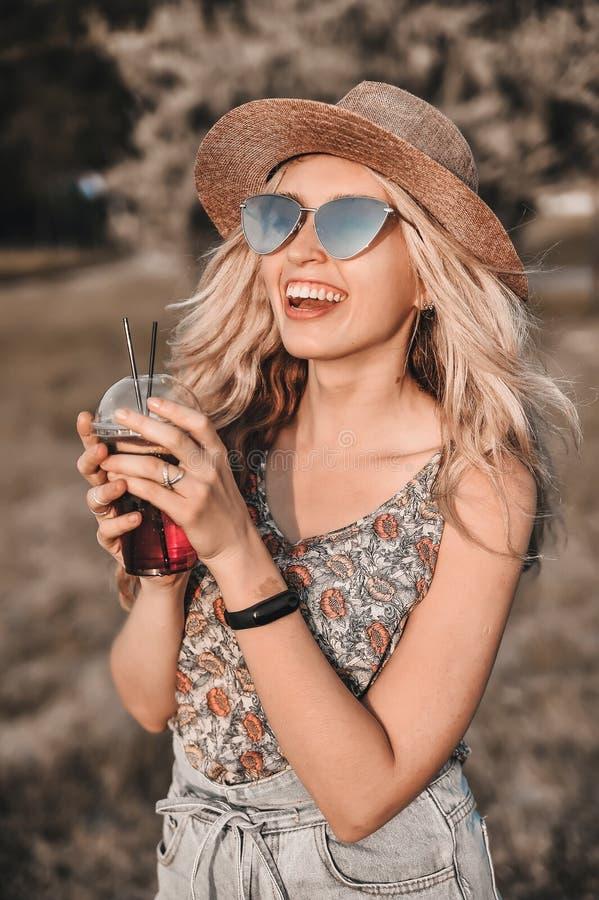 Красивая молодая женщина в стильной шляпе с холодным коктейлем имеет outdoors потехи стоковые фотографии rf