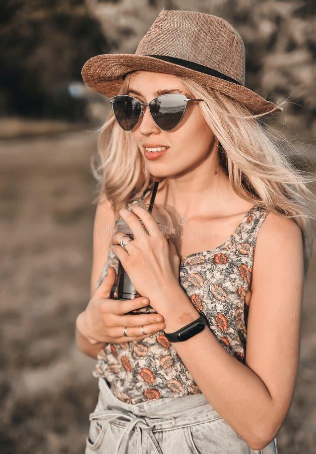 Красивая молодая женщина в стильной шляпе с холодным коктейлем имеет outdoors потехи стоковые фото