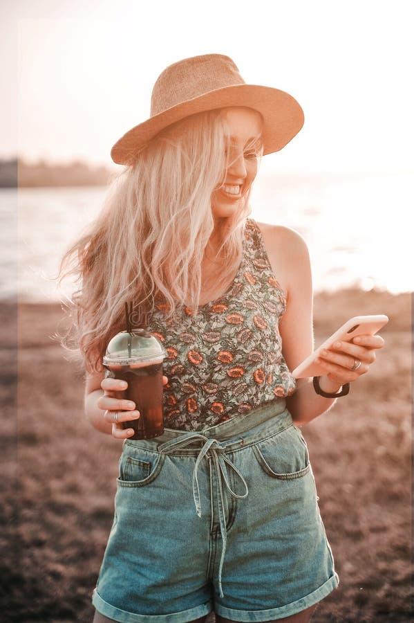 Красивая молодая женщина в стильной шляпе с холодным напитком лета имеет outdoors потехи стоковые изображения