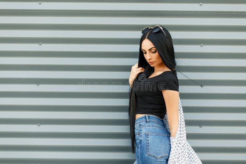 Красивая молодая женщина в черной стильной футболке и голубых джинсах стоковые изображения