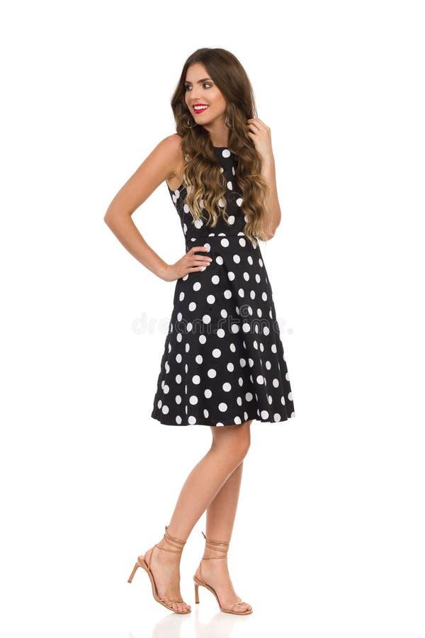 Красивая молодая женщина в черном платье коктейля в точках польки и бежевых сандалиях высоких пяток стоящ и смотрящ прочь стоковая фотография