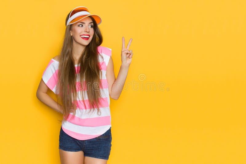 Красивая молодая женщина в Striped рубашке и забрале Солнця показывает знак мира руки стоковое фото rf