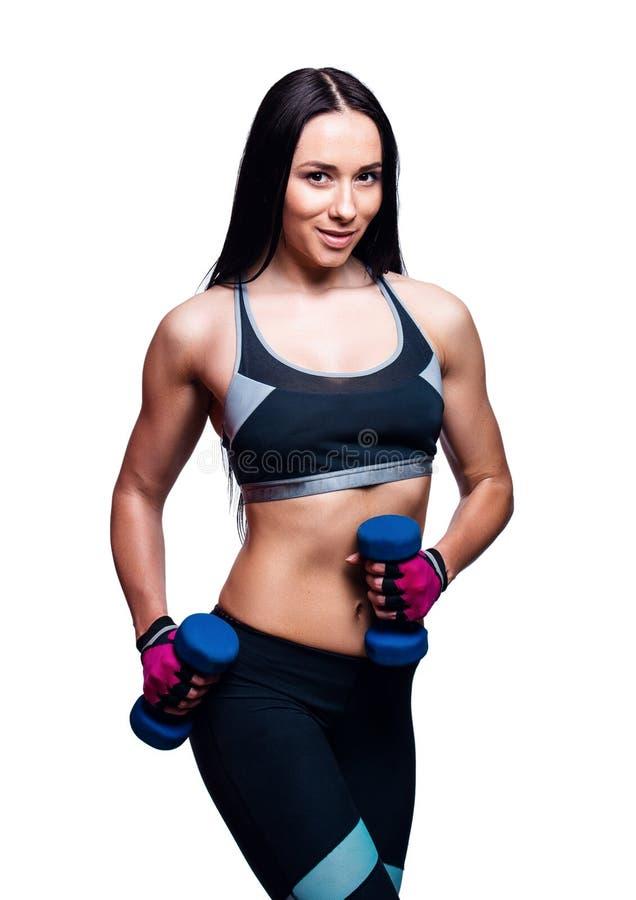 Красивая молодая женщина делает тренировки с гантелями в студии Sporty атлетическая девушка поднимаясь вверх по весам против бело стоковое изображение rf