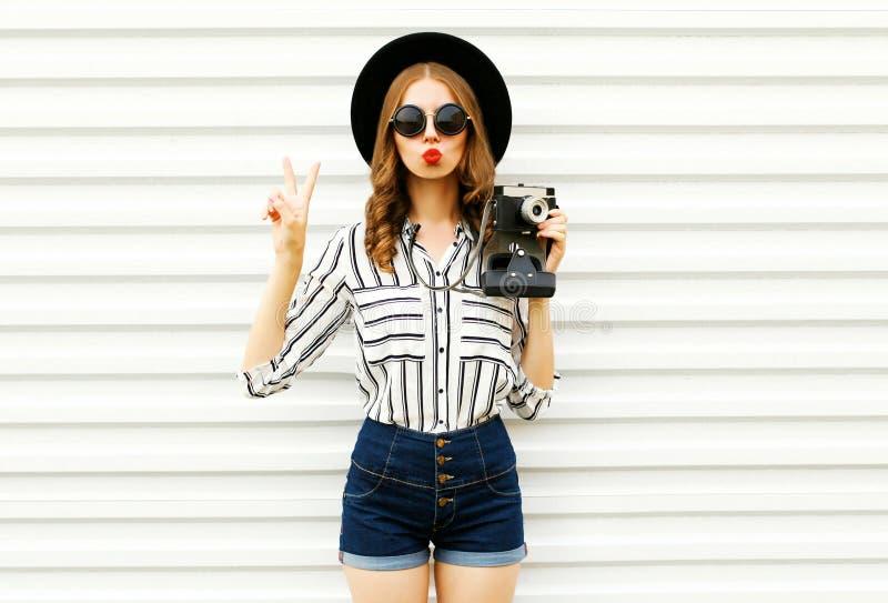 Красивая молодая женщина держа винтажную камеру фильма, отправляя сладкий поцелуй воздуха в черной круглой шляпе, шорты, белая st стоковая фотография rf