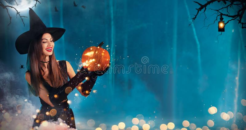 Красивая молодая женщина держа высекаенную тыкву стоковое фото rf