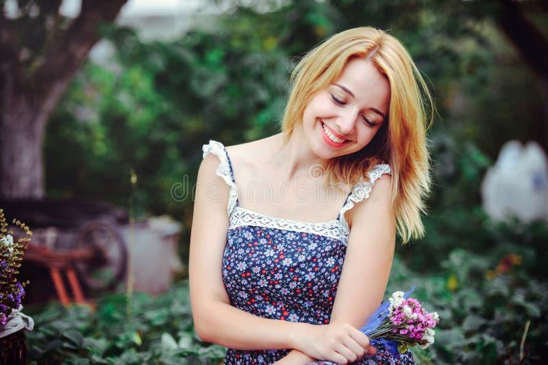 Красивая молодая женщина имея пикник в сельской местности Счастливый уютный день outdoors открыто Усмехаясь женщина с wildflowers стоковые фотографии rf