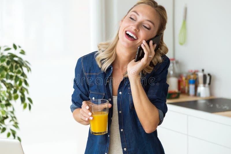 Красивая молодая женщина используя ее мобильный телефон в кухне стоковое изображение rf