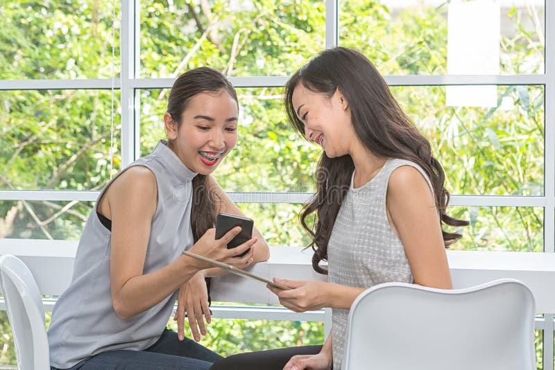 Красивая молодая женщина используя цифровые мобильный телефон и планшет в кофейне Друзья используя смартфон и планшет в баре Женщ стоковые изображения