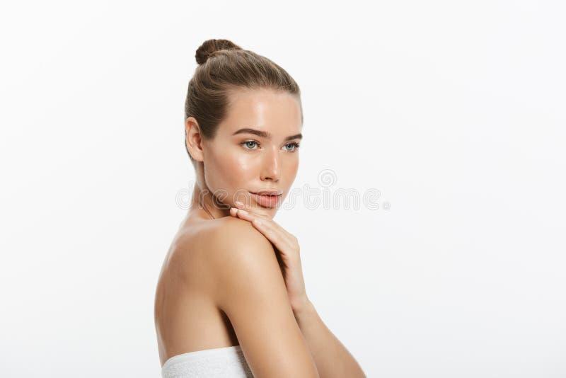 Красивая молодая женщина касаясь ее коже Принципиальная схема заботы красоты и кожи стоковое фото