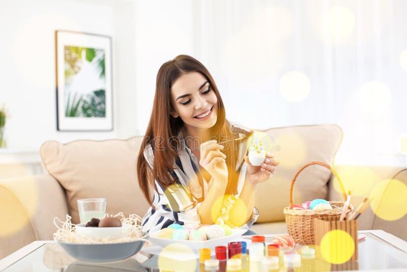 Красивая молодая женщина крася пасхальные яйца дома стоковые изображения rf
