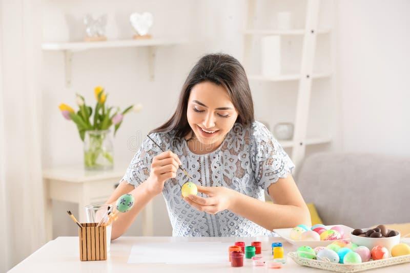 Красивая молодая женщина крася пасхальные яйца дома стоковые фото