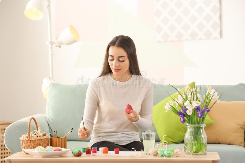 Красивая молодая женщина крася пасхальные яйца дома стоковые изображения
