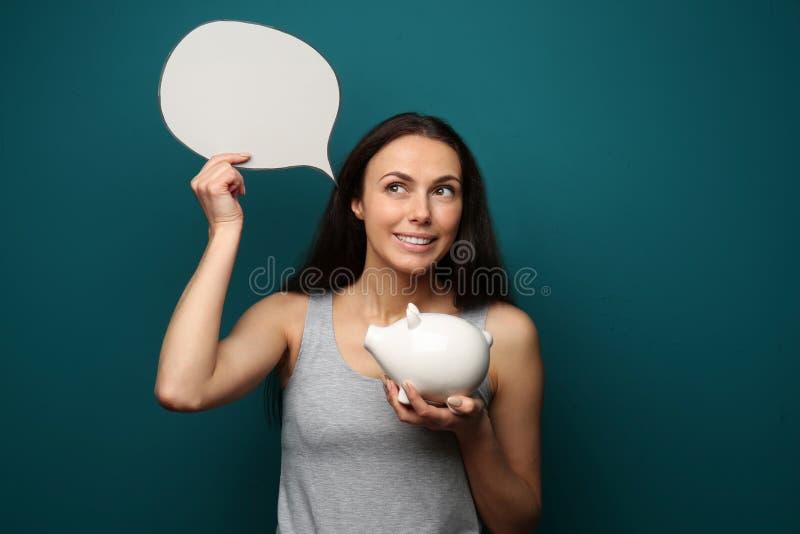 Красивая молодая женщина мечтая о будущих приобретениях на предпосылке цвета стоковые фото