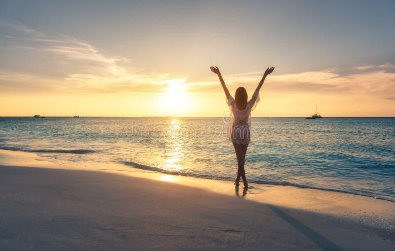 Красивая молодая женщина на песчаном пляже на заходе солнца стоковая фотография rf