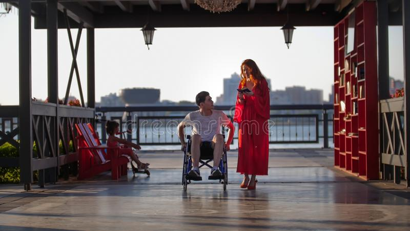 Красивая молодая женщина на прогулке с молодым человеком в кресло-коляске в вечере лета стоковая фотография rf