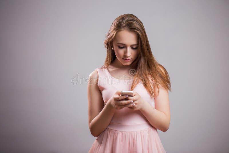 Красивая молодая женщина носит розовое платье и использует smartphone на серой предпосылке с космосом экземпляра стоковое изображение rf