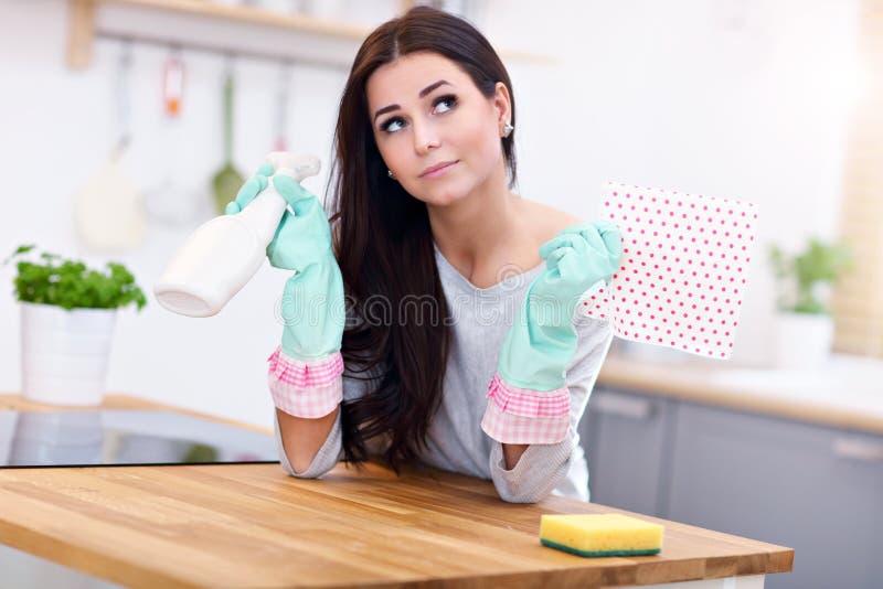 Красивая молодая женщина очищая кухню стоковые изображения
