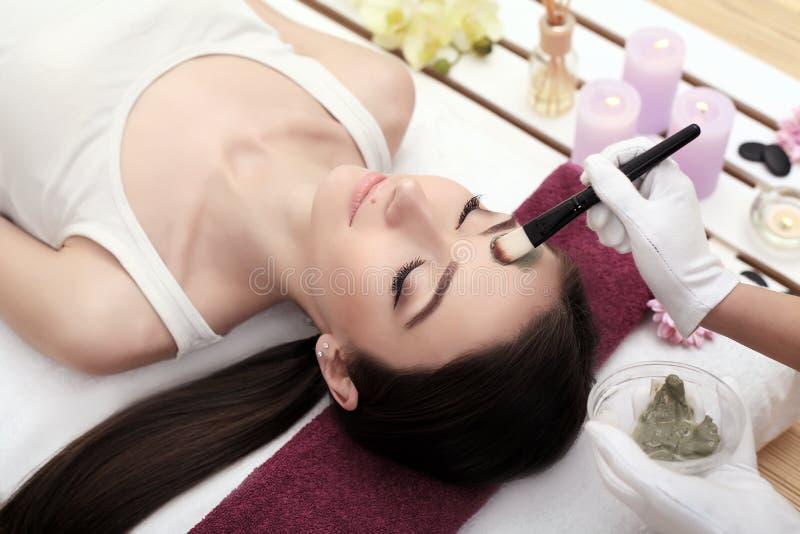 Красивая молодая женщина получает лицевую маску глины на курорте, лежа стоковые фотографии rf