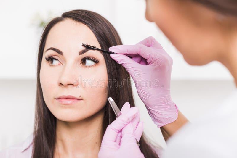 Красивая молодая женщина получает процедуру по коррекции брови стоковые фотографии rf