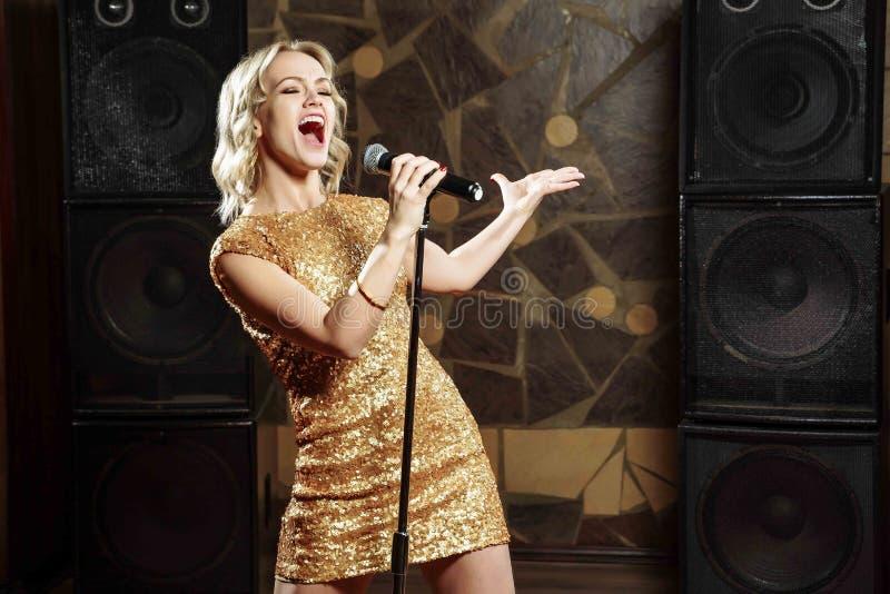 Красивая молодая женщина поя с микрофоном стоковая фотография rf