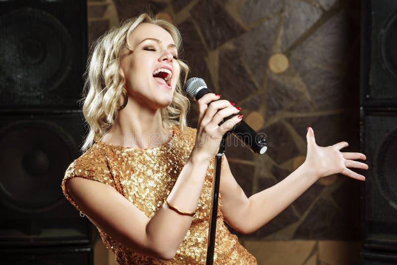 Красивая молодая женщина поя с микрофоном стоковые изображения rf