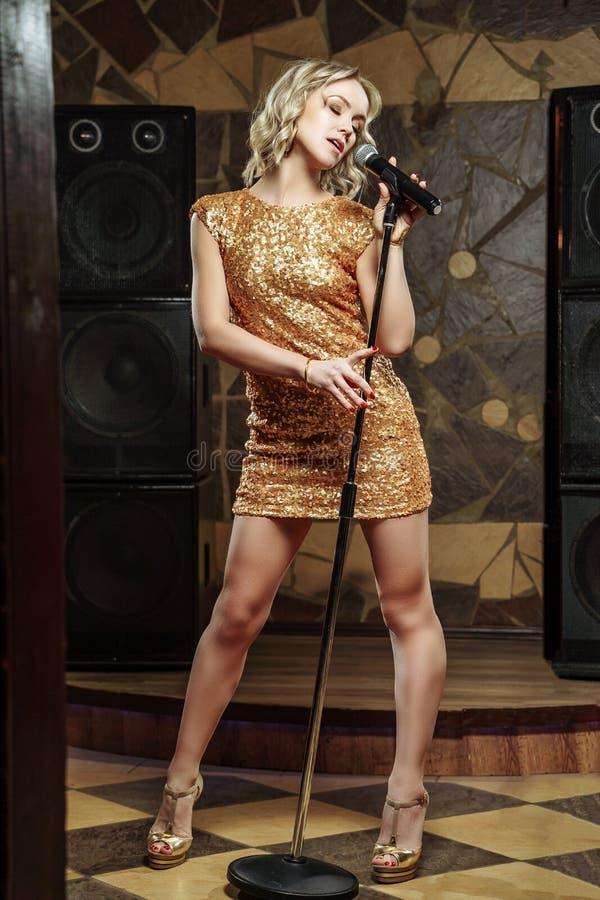 Красивая молодая женщина поя с микрофоном стоковое фото rf