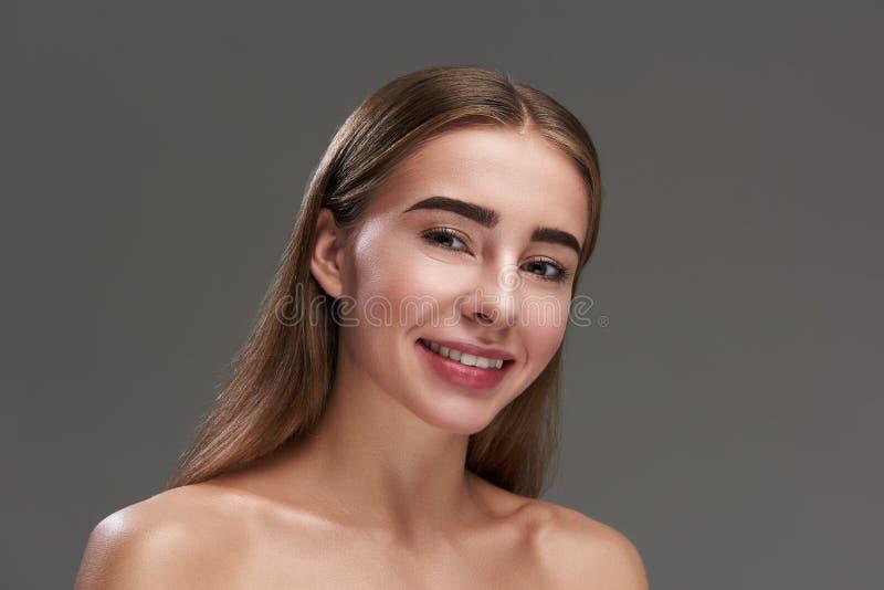 Красивая молодая женщина представляя против серой предпосылки стоковые фото