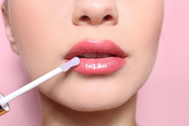Красивая молодая женщина прикладывая лоск на ее совершенных губах стоковые изображения