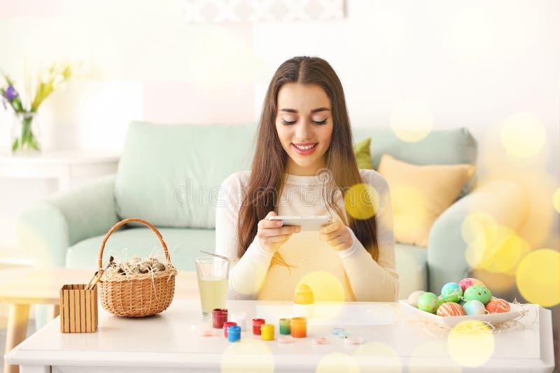 Красивая молодая женщина принимая фото покрашенных пасхальных яя дома стоковые фотографии rf
