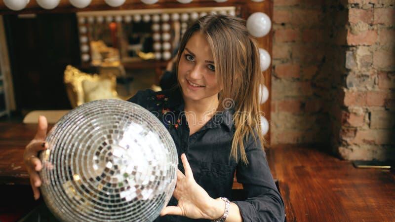Красивая молодая женщина при шарик диско представляя и усмехаясь в студии внутри помещения стоковое изображение rf