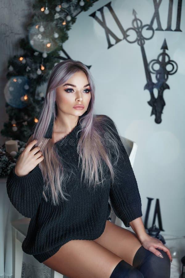 Красивая молодая женщина сидя на предпосылке большого оформления рождества часов, держащ электрофонарь, ждать праздник стоковое изображение