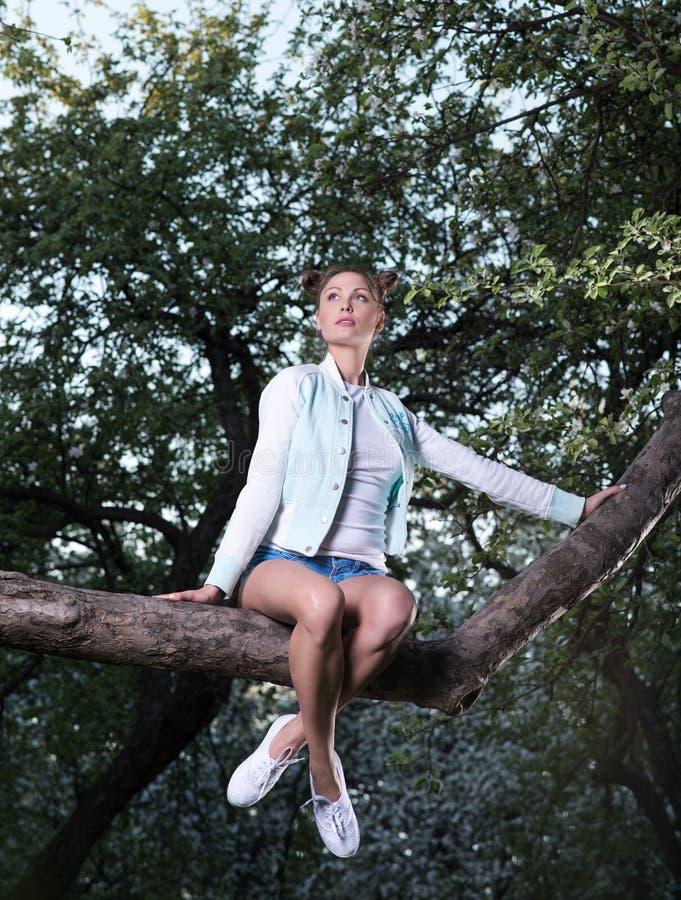 Красивая молодая женщина сидя на саде ветви дерева весной стоковое изображение