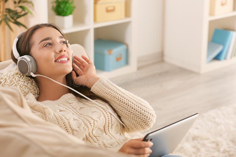 Красивая молодая женщина слушая музыку дома стоковые фотографии rf