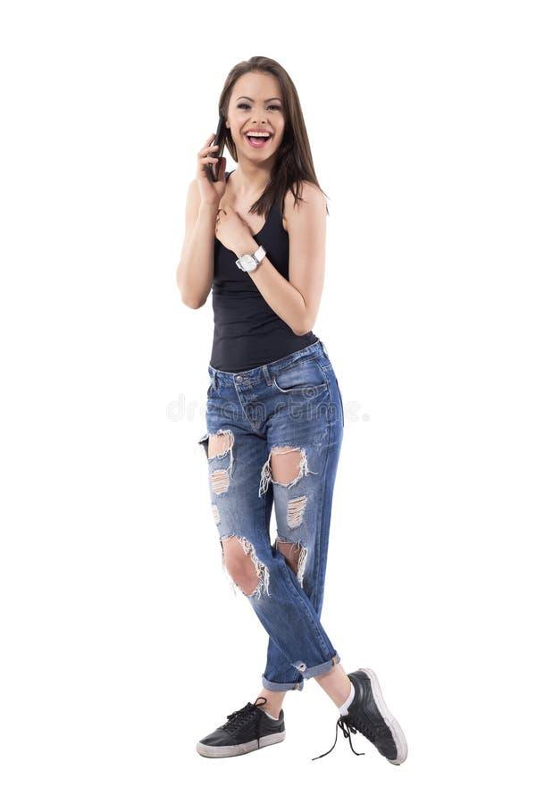 Красивая молодая женщина смеясь heartily пока говорящ на мобильном телефоне стоковые фото