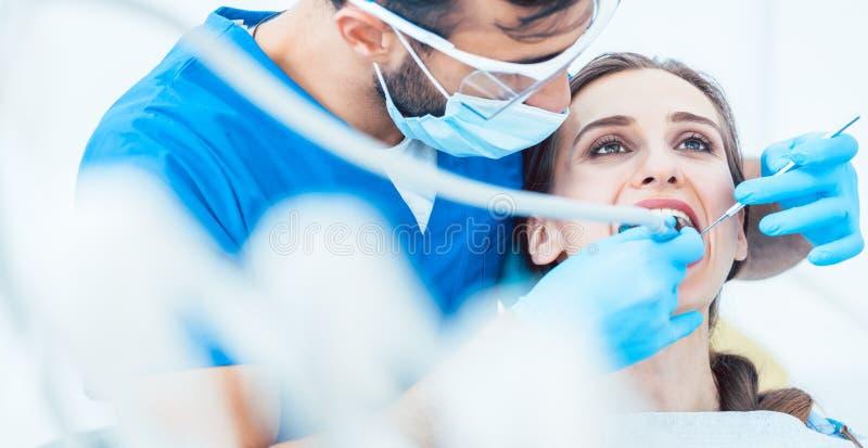 Красивая молодая женщина смотря вверх ослабила во время безболезненной зубоврачебной процедуры стоковая фотография rf