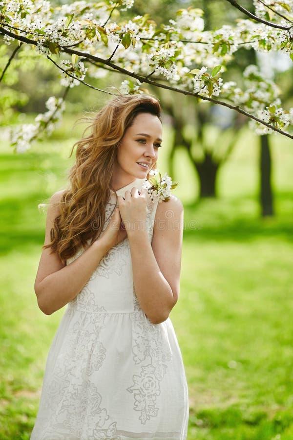 Красивая молодая женщина со светлыми волосами в модном белом платье представляя около цветя дерева на зацветая саде на стоковые фотографии rf