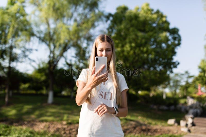 Красивая молодая женщина со светлыми волосами используя мобильный телефон на открытом воздухе Стильная девушка делая selfie стоковые изображения