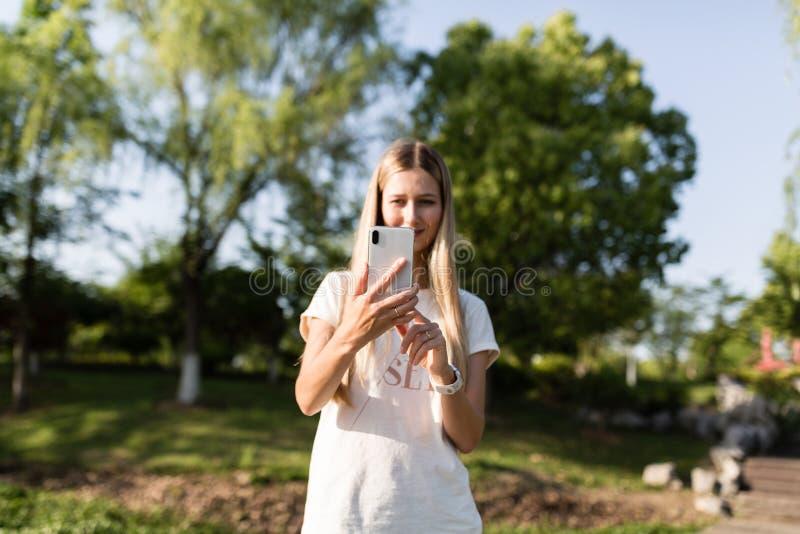Красивая молодая женщина со светлыми волосами используя мобильный телефон на открытом воздухе Стильная девушка делая selfie стоковая фотография rf