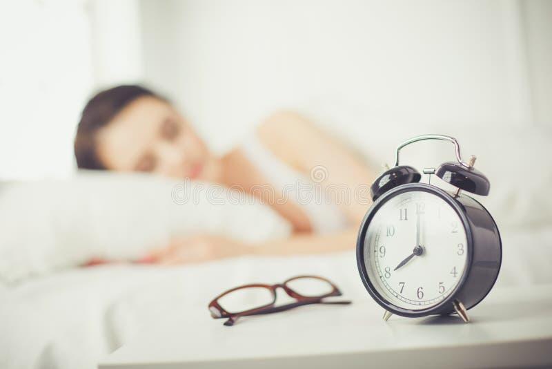 Красивая молодая женщина спать пока лежащ в кровати удобно и блаженно на предпосылке будильника стоковое изображение rf