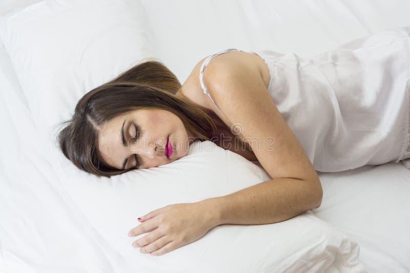 Красивая молодая женщина спящ очень расслабленная на белой кровати стоковая фотография rf
