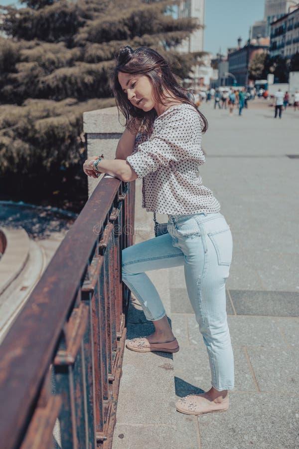 Красивая молодая женщина с близкими глазами думая и отдыхая на перилах около королевского дворца Мадрида, Испании стоковое изображение rf