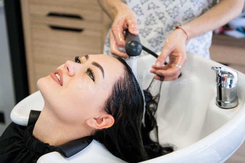 Красивая молодая женщина с головой парикмахера моя на парикмахерской стоковые изображения rf