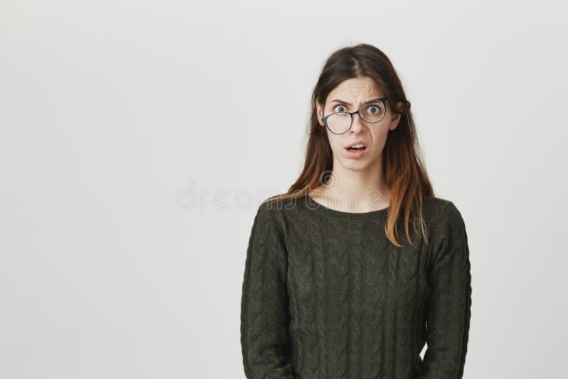 Красивая молодая женщина с длинными прямыми волосами, носит зрелища и зеленый свитер будучи сотрясенной и оглушенные с новостями стоковые изображения rf