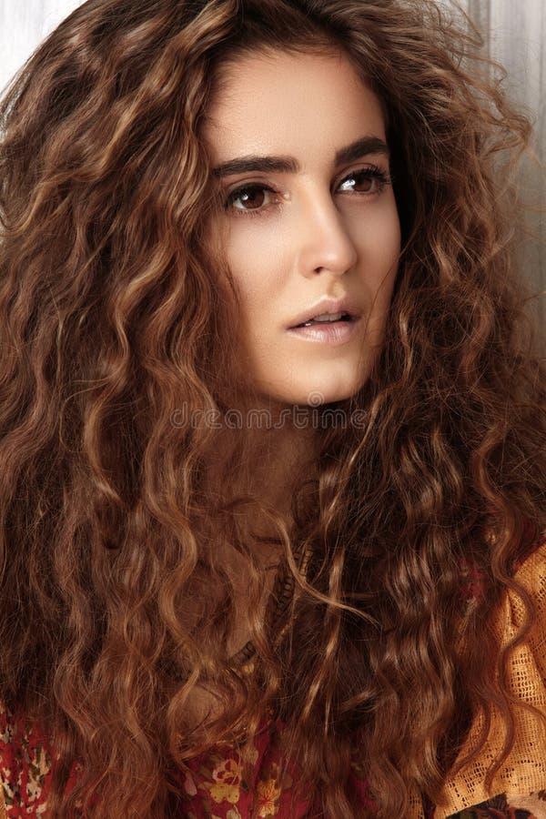 Красивая молодая женщина с длинным курчавым стилем причёсок, ювелирными изделиями моды с волосами брюнет Индийские одежды стиля,  стоковое фото